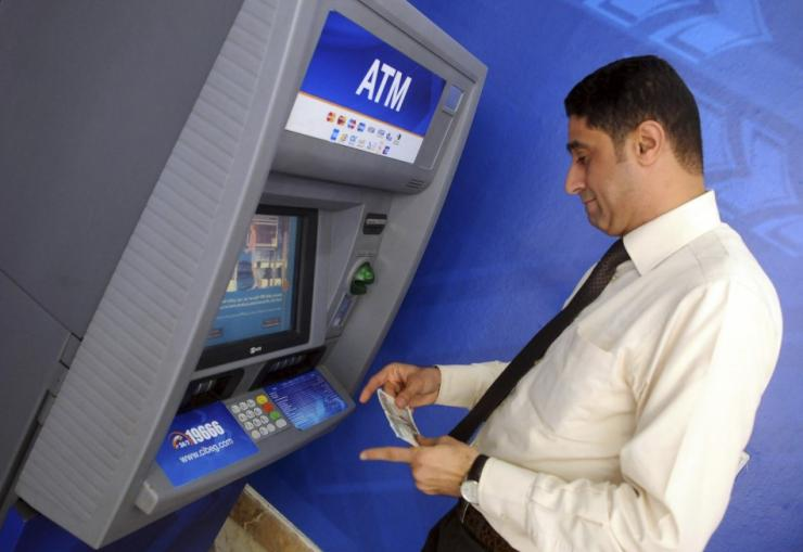 A man withdraws money from an ATM machine