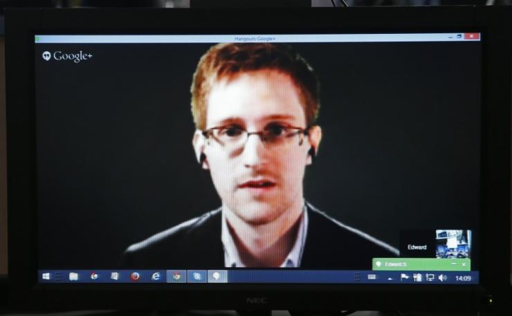 Accused government whistleblower Edward Snowden is seen on a screen as he speaks via video conference
