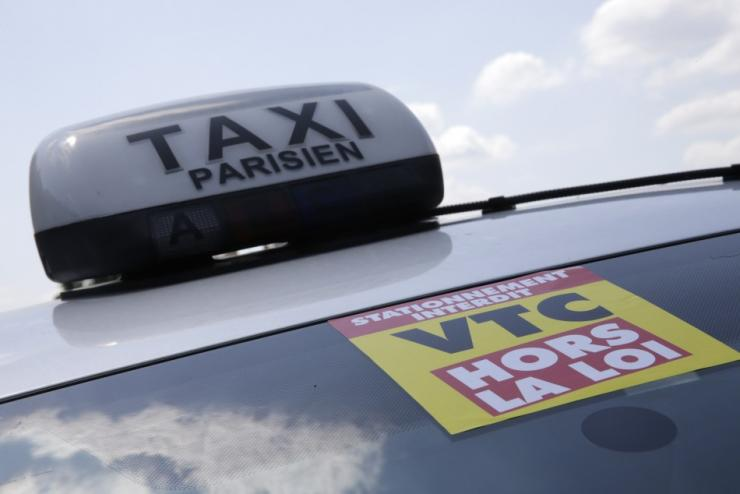A yellow ribbon indicates a striking Paris taxi which takes part in a demonstration in the French capital June 11, 2014.