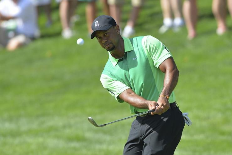 Jun 26, 2014; Bethesda, MD, USA; Tiger Woods chips onto the green on the 15th hole during the first round of the Quicken Loans National golf tournament at Congressional Country Club - Blue Course.