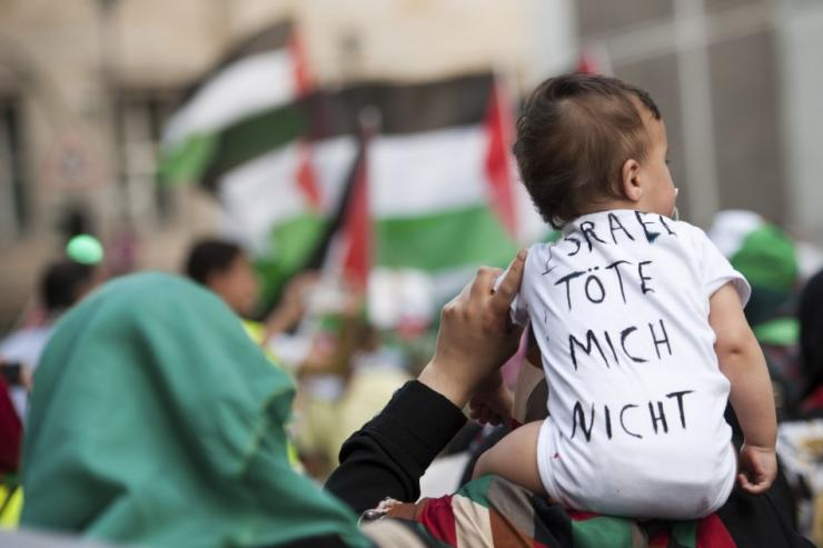 "A woman carries a baby with shirt that reads, ""Israel don't kill me"", during a demonstration supporting Palestine, in Berlin"