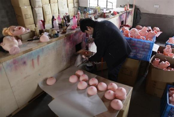 A worker sprays pink color on a nipple of an unfinished breast for an inflatable sex doll at Ningbo Yamei plastic toy factory, on the outskirts of Fenghua, Zhejiang province, February 13, 2012.