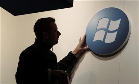 A Worker Adjusts A Logo On The Microsoft Stand
