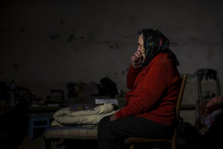 A woman sits inside a basement used as a shelter from the recent shelling