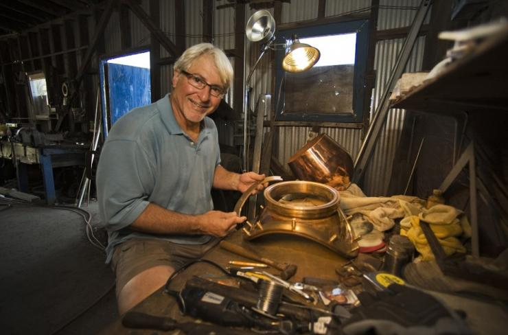 Nicholas Toth works on a breast plate for a diving helmet at his workshop next to the Anticlote River in Tarpon Springs, Florida, April 6, 2014. Toth is among the last to carry on the century-old family skill of hand crafting helmets for sponge divers. He