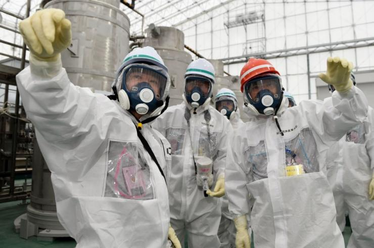 Japan's new Economy, Trade and Industry Minister Yoichi Miyazawa (R), wearing a protective suit and a mask, inspects the Tokyo Electric Power Co. (TEPCO)'s tsunami-crippled Fukushima Daiichi nuclear power plant in Fukushima prefecture, in this p
