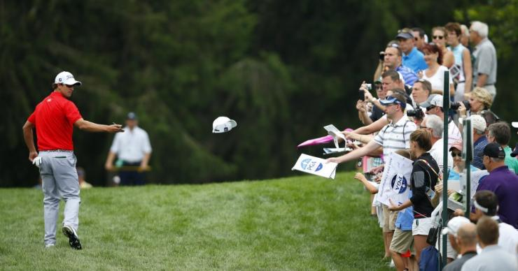 Australia's Adam Scott tosses a hat he autographed to the gallery as he walks on the 17th hole during a practice round for the 2013 PGA Championship golf tournament at Oak Hill Country Club in Rochester, New York August 7, 2013.