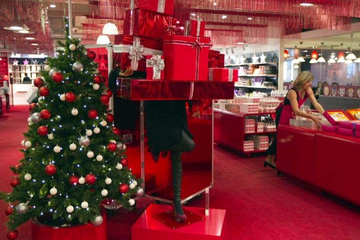 An employee in the toy section of the Galeries Lafayette department store arranges a display near a Christmas tree in preparation for holiday season gift shopping in Paris November 17, 2011.