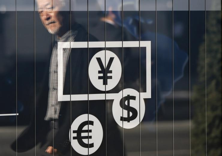 Passers-by are reflected on a signboard displaying currency signs outside a bank in Tokyo November 27, 2014. The dollar edged down against the yen on Thursday after lacklustre U.S. economic data pushed Treasury yields lower and dulled investor appetite fo