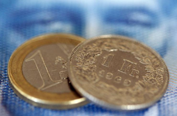 An one euro coin and an one Swiss franc coin are seen on a one hundred Swiss franc note, in this picture illustration taken in Zurich August 8, 2011. The safe-haven Swiss franc and  the yen soared on Monday after Standard