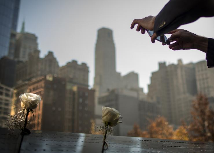 A man takes a picture of a flower placed on a name at the 9/11 Memorial in New York November 10, 2014. The 9/11 Memorial is holding a Salute to Service, a five day tribute to veterans for Veterans Day.