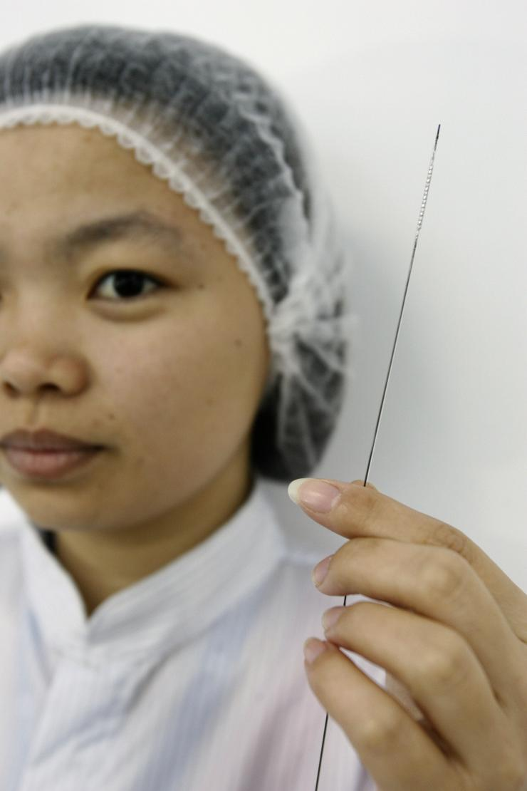 A lab technician poses with a stent