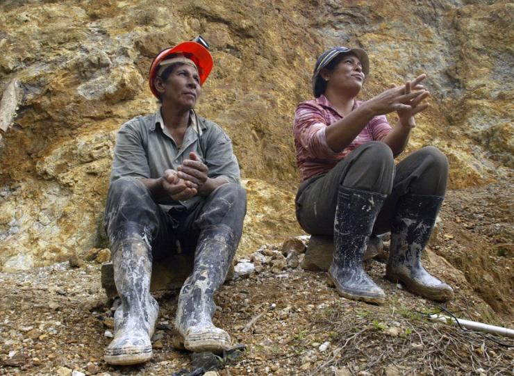 Two women rest outside the tunnel entrance of the Santa Elena mine after putting in their day's work, December 5, 2006.