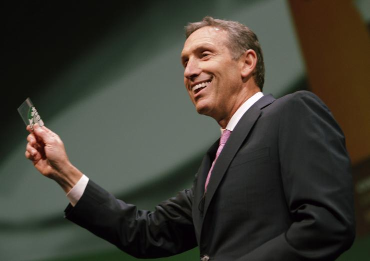 Starbucks CEO Howard Schultz holds up a Starbucks Card as he speaks to shareholders at the company's annual meeting of shareholders in Seattle, Washington March 23, 2011.