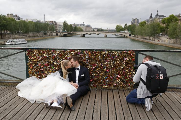 "A recently-married couple from Poland, Dominika and Bartek Mieczkowski, kiss as they pose for their own photographer in front of an iron grill covered with ""love locks"" on the Pont de Arts over the River Seine in Paris, France, May 31, 2015."