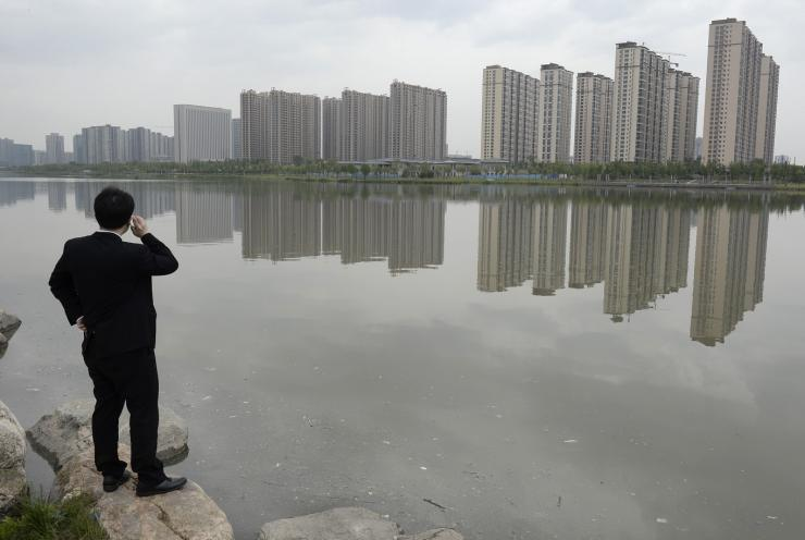 A man talks on his phone near a new residential compound in Taiyuan, Shanxi province, May 11, 2014.