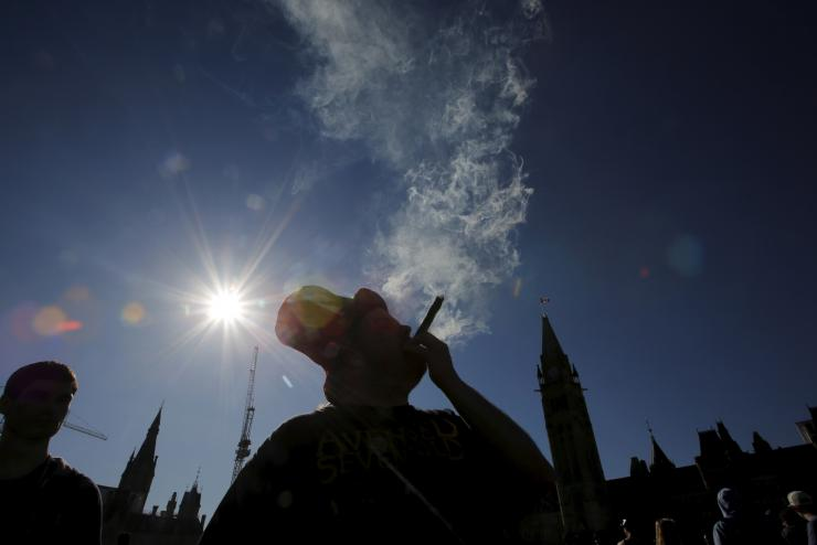 A man smokes marijuana during an annual 4/20 rally on Parliament Hill in Ottawa, Canada, April 20, 2016.