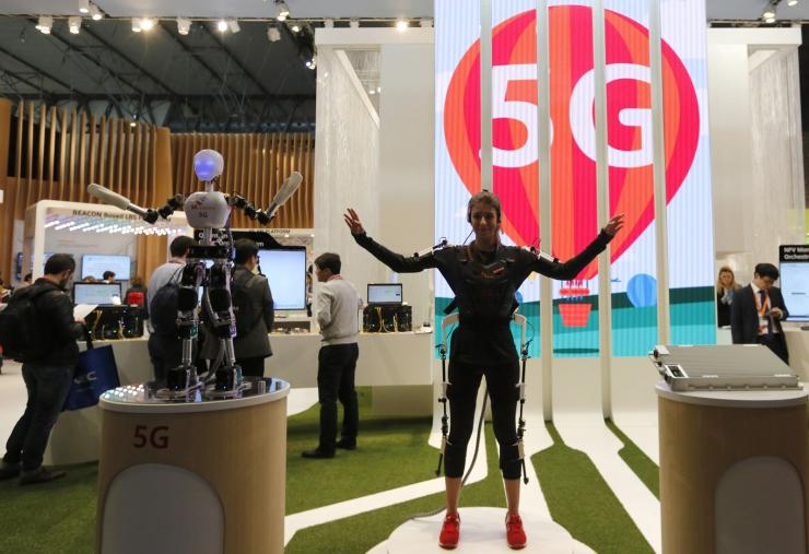 An SK telecom exhibitor directs the robot's movements using 5G on the last day at the Mobile World Congress in Barcelona March 5, 2015.