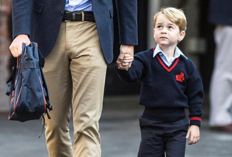 Prince George holds his father Britain's Prince William's hand as he arrives on his first day of school at Thomas's school in Battersea, London, September 7, 2017.
