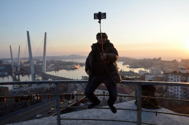 A man takes a selfie against Golden Horn Bay in the city of Vladivostok, Russia February 19, 2018.