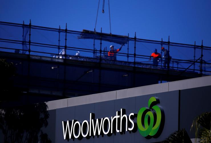 Workers can be seen on a building site behind a Woolworths Ltd supermarket, Australia's biggest grocery chain by sales, located in Sydney, Australia, August 23, 2017.