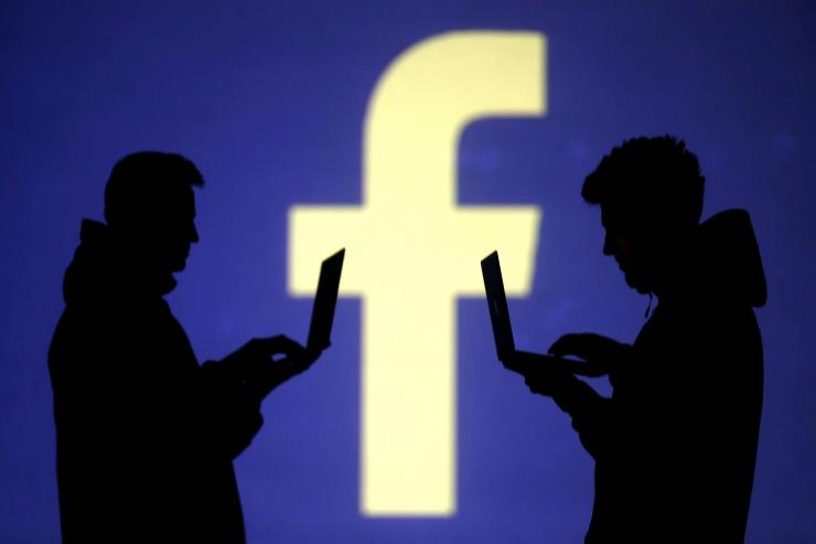 FILE PHOTO: Silhouettes of laptop users are seen next to a screen projection of Facebook logo in this picture illustration taken March 28, 2018.