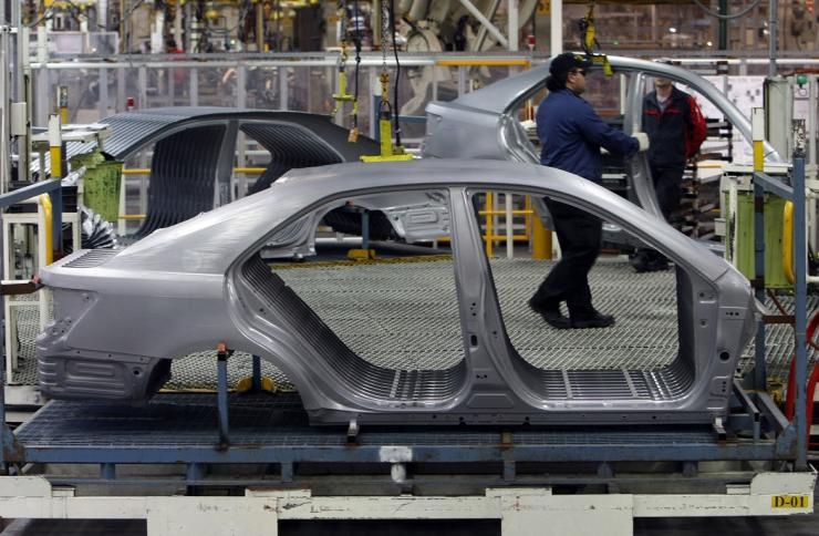 An Auto worker loads bodyshells of a Toyota Camry Hybrid car onto the assembly line at the Toyota plant in Melbourne August 31, 2009.