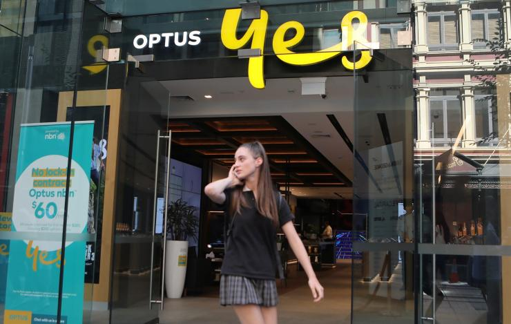 A woman uses her mobile phone as she walks past in front of an Optus shop in Sydney, Australia, February 8, 2018.