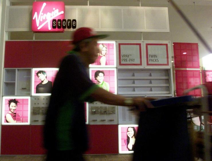 A cleaner walks past a Virgin Mobile stand at a shopping complex in Singapore July 24, 2002.
