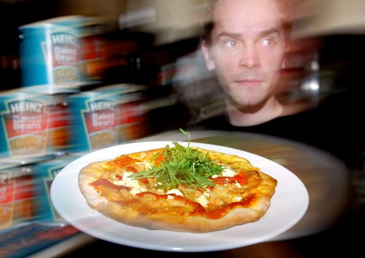 "Waiter Will Phillips delivers a baked beans pizza at a new restaurant called ""Beans Meanz Heinz"" in Melbourne May 26, 2004."