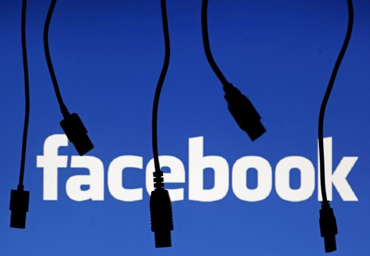 Electronic cables are silhouetted next to the logo of Facebook in this September 23, 2014 illustration photo in Sarajevo.