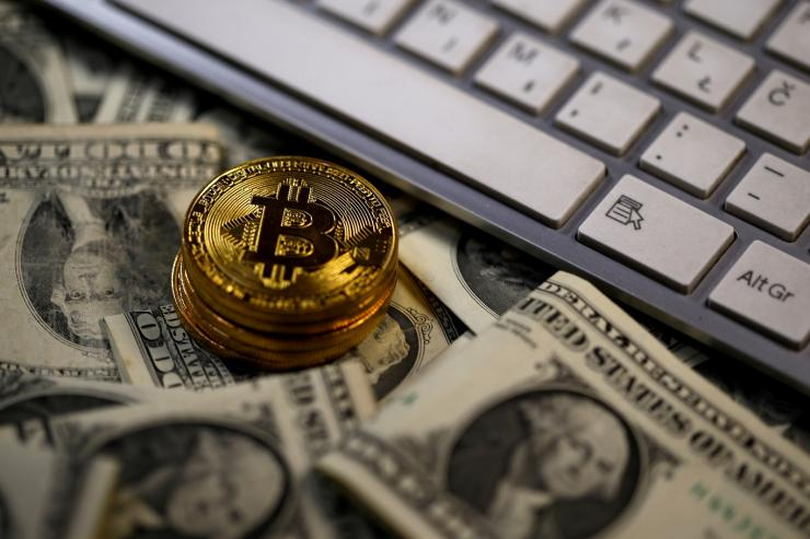 FILE PHOTO: Bitcoin (virtual currency) coins placed on Dollar banknotes, next to computer keyboard, are seen in this illustration picture, November 6, 2017.
