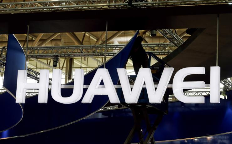 FILE PHOTO: A worker adjusts the logo at the stand of Huawei at the CeBIT trade fair in Hanover, in this file picture taken March 15, 2015.
