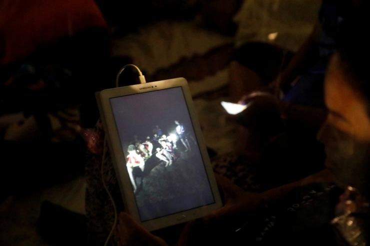 A family member looks at a photo near Tham Luang cave complex, as members of under-16 soccer team