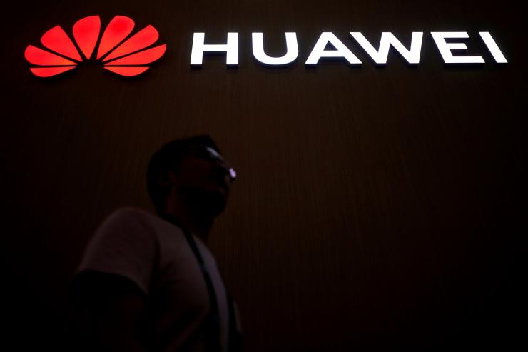 FILE PHOTO: A man walks past a sign board of Huawei at CES (Consumer Electronics Show) Asia 2018 in Shanghai, China June 14, 2018.