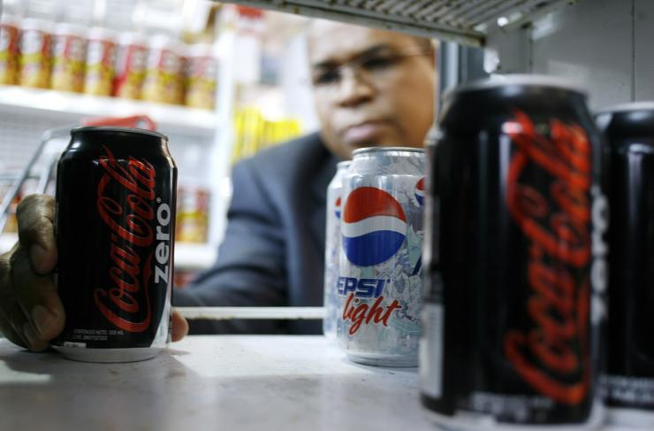 A man poses with a Coca Cola Zero can at a supermarket in Caracas June 11, 2009.