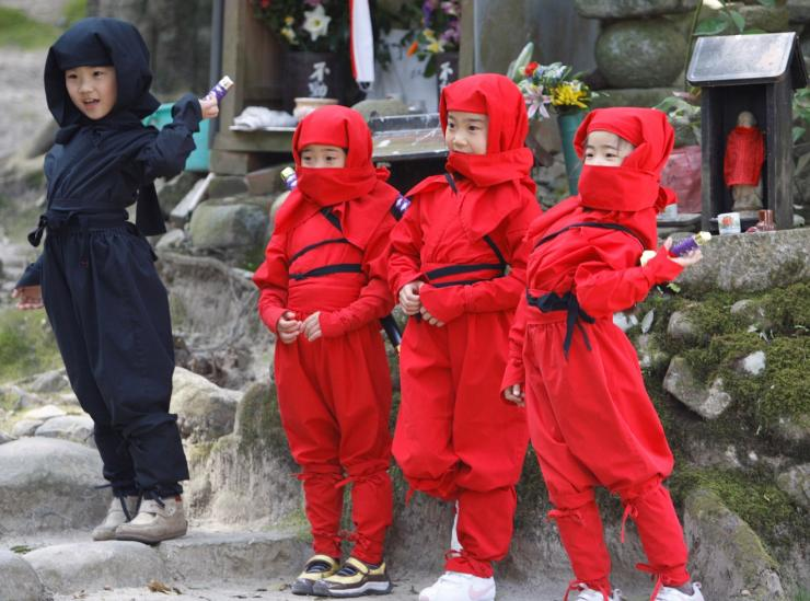 FILE PHOTO: Children dressed as ninjas pose for a souvenir picture during a ninja festival in Iga, about 450 km (280 miles) from Tokyo, April 6, 2008.