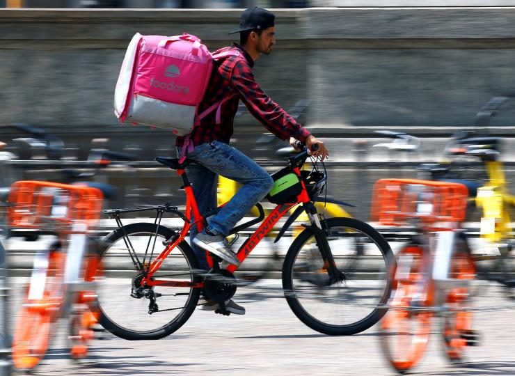 A food delivery driver for Foodora cycles in downtown Milan, Italy, May 18, 2018.