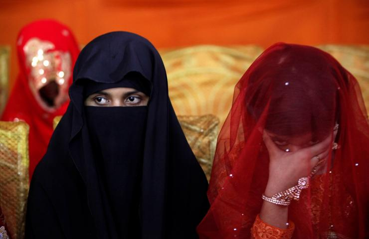 A bride sits with a companion during a mass wedding ceremony in Karachi, Pakistan May 9, 2016.