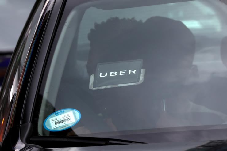 FILE PHOTO: An Uber logo is seen on a car as it car drives through Times Square in New York City, New York, U.S., July 27, 2018.