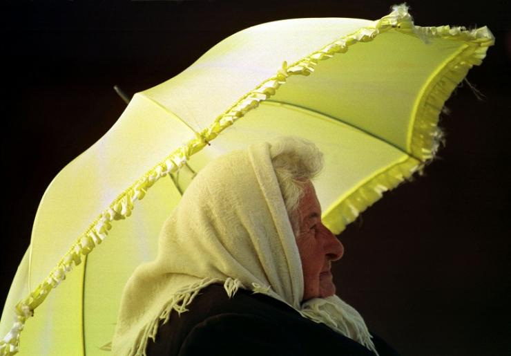 An elderly lady shields herself from the sun with an umbrella while waiting for a bus in Sydney October 14.