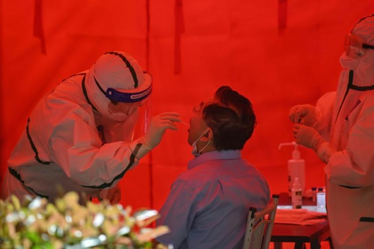 A medical worker takes a swab sample from a man to test for the COVID-19 coronavirus in Wuhan, in China's central Hubei province