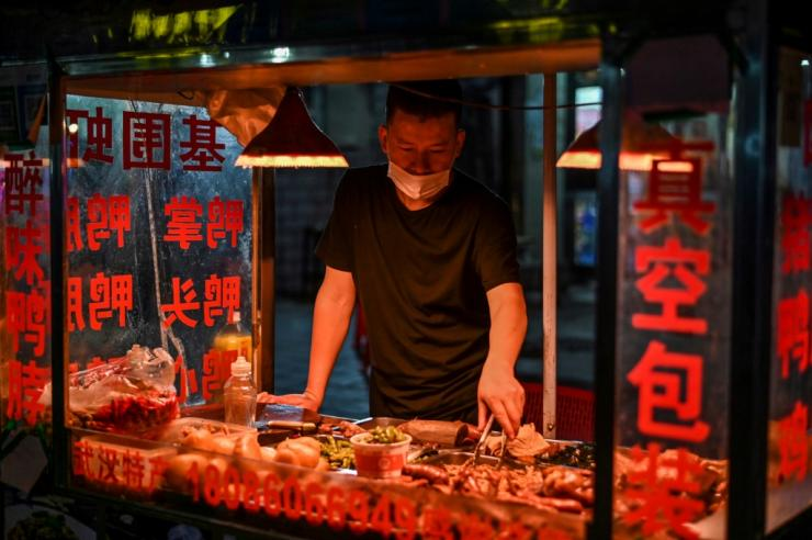 A man wearing a facemask sells food at his stall on a street in Wuhan, China