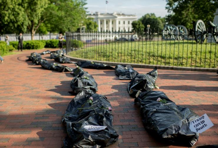 Demonstrators display fake body bags during a protest in front of the White House in Washington, DC