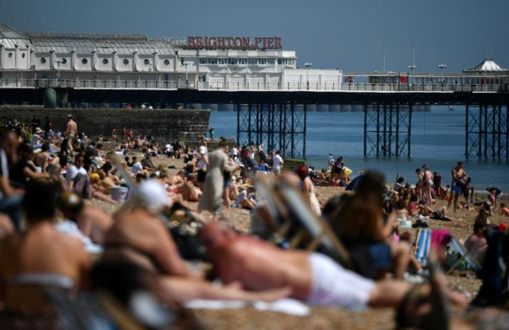 People enjoy the sunshine on the beach in Brighton, on the south coast of England, as the country's official coronavirus death toll rose to 25,079