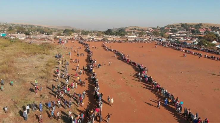 Thousands of people queue up in the early morning in the informal settlement of Iterileng, Pretoria, to receive food hampers, masks, soap and hand sanitiser during South Africa's coronavirus lockdown.