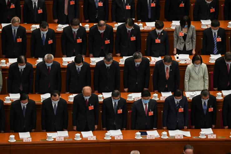 Delegates wearing face masks stand in a silent tribute for victims of the COVID-19 coronavirus during the opening session of the National People's Congress (NPC) at the Great Hall of the People in Beijing