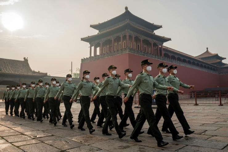 People's Liberation Army soldiers march next to the entrance to the Forbidden City during the opening ceremony of the Chinese People's Political Consultative Conference (CPPCC) in Beijing