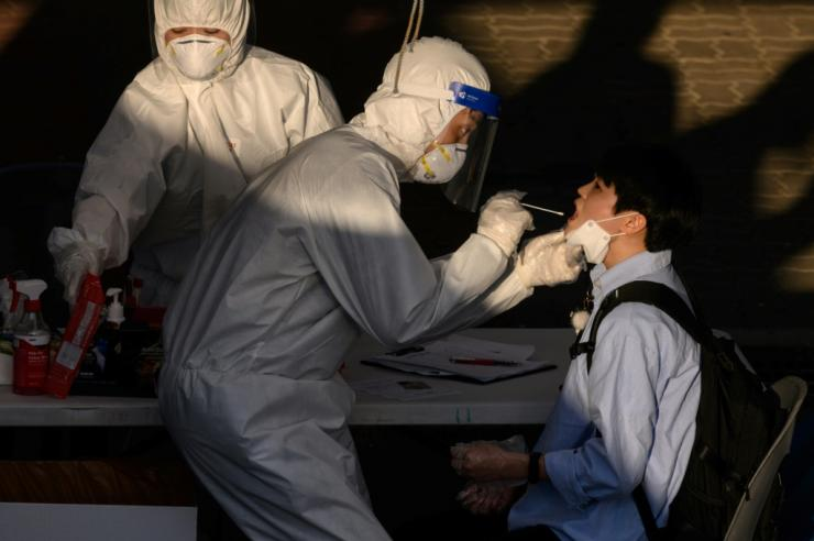 A South Korean health worker tests a man at a temporary COVID-19 testing centre in Bucheon, south of Seoul -- the country is reimposing some lockdown measures after a spate of new infections cropped up