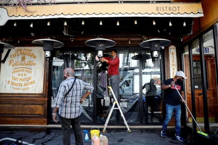 Employees clean the terrace of a Paris cafe ahead of reopening in early June 2020
